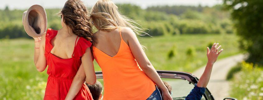 Glückliche Freund fahren mit Auto im Sommer